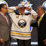 Sam Reinhart, center puts on a Buffalo Sabres cap after being selected as the No. 2 overall pick in the 2014 NHL draft on June 27.