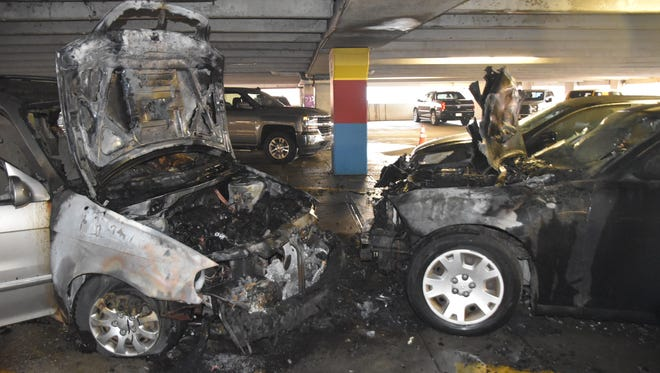 Flames engulfed these two vehicles in a Downtown parking garage on Monday.