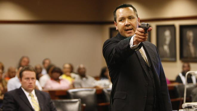 Kenton County Commonwealth's Attorney Rob Sanders pulls the trigger of an empty .45-caliber handgun during a trial.