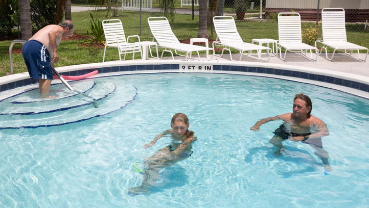 """Larry Peake, right, a resident of Caribbean Park for three years, swims at the community swimming pool with his granddaughter Olyvia Lebasseur on Tuesda in Naples. The park was recently purchased by Zeman Homes, a Chicago-based realty group, causing concern for some of the residents of the park. """"None of it is bothering me,"""" Peake said. """"Nothing has really changed."""""""