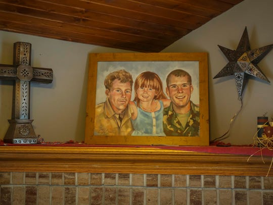 Paul Byers, left, Hailey Byers and her father, Casey Byers, in a composite painting done by a friend that sits in her home in Le Mars, Iowa, May 8, 2018. She never met her father, Casey Byers, who was killed in action while serving in Iraq. She's being raised in Le Mars by his parents, Bill and Ann Byers.