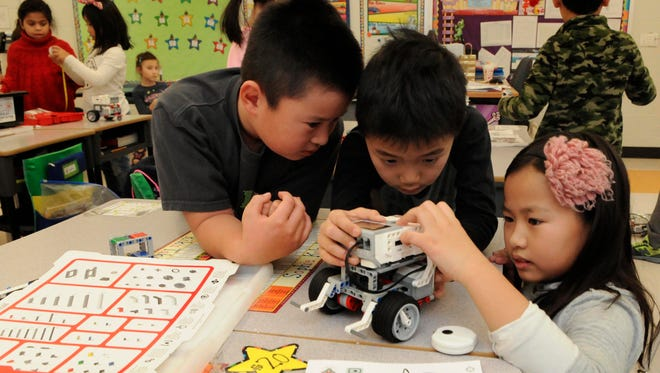 George Washington School second-graders,  from left,  Kotero Fujiwara, Riko Takano and Sophie Kakuda learning how to build and program Lego Mindstorms robots.