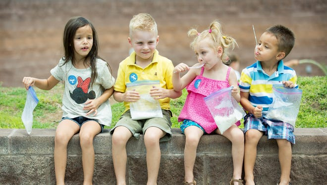 Friends, from left, Sophia Davila, 6, Ryker Crowley, 4, Ansli Crowley, 2, and Bane Davila, 4, together enjoy ice cream made by hand in a plastic bag on Sunday, July 16, 2017, during the 14th annual Ice Cream Sunday at the New Mexico Farm and Ranch Heritage Museum.