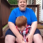 Lisa Smith sits on her porch, with son Noah, at their home Belleville, Mich. Noah is registered to use marijuana to control epileptic seizures; the effect on his autism was an unexpected benefit. Smith is asking the state of Michigan to add autism to the list of conditions that qualify for medical marijuana.