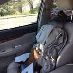 This photo provided by the Suffolk County Police shows a fake front seat passenger, complete with briefcase and baseball cap — but no seatbelt — in a car that police pulled over Thursday morning during rush hour on the Long Island Expressway in Dix Hills, N.Y. Authorities say they've ticketed the woman driving the vehicle.