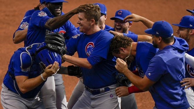Chicago Cubs starting pitcher Alec Mills is swarmed by teammates after throwing a no hitter Sunday in Milwaukee.