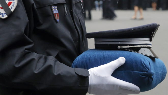 A French police officer holds the hat of late police officer Ahmed Merabet during a Jan. 13 ceremony to pay tribute to the three officers killed in recent terror attacks: Merabet, 40, and officer Franck Brinsolaro, 49, were killed in the attack at Charlie Hebdo, and Clarissa Jean-Philippe was killed in Montrouge.