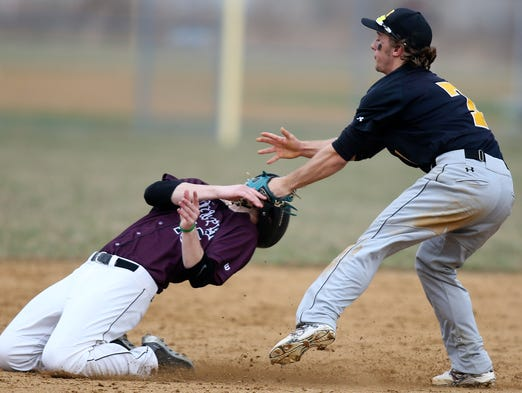 Appoquinimink's Joe Otto is caught with a high tag as Newark shortstop Matt Fleming puts him out on a grounder near the bag in the third inning of Newark's 6-2 win Thursday, April 3, 2014 at Appoquinimink High School.