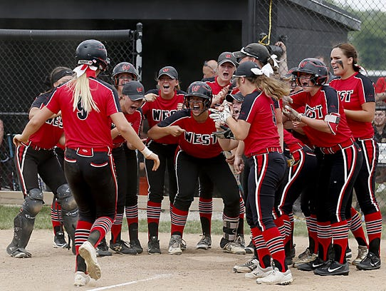 Alyssa Triner (9) is greeted at home plate by her Lakota
