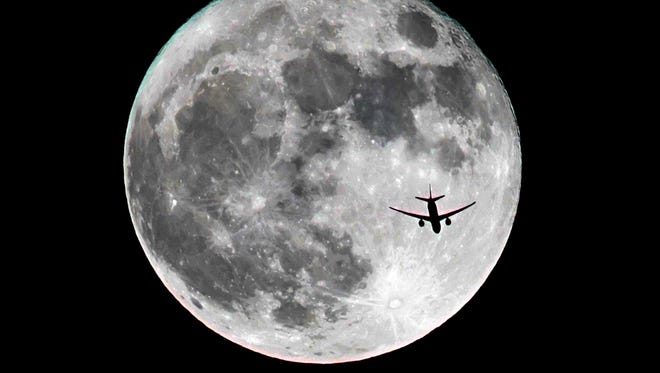 This photo captures the November supermoon with an airliner passing overhead Monday evening.