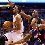 March 2, 2014 - Suns' Ish Smith goes for the basket against Hawks' Elton Brand (top) and Jeff Teague (bottom) at US Airways Center.