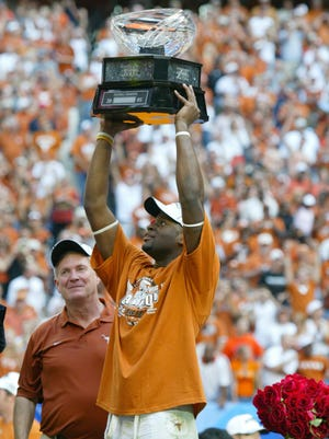 Texas quarterback Vince Young hoists the Big 12 trophy after the Longhorns destroyed Colorado 70-3 in 2005.