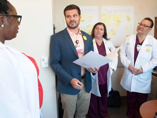 Research program manager Andrew March, 2nd from left, has a discussion with (far left) research coordinator Jacquelyn Thomas, clinical research coordinator Robin Turton and research coordinator Maria Snyder at MD Anderson Cancer Center at Cooper in Camden, on July 13, 2018.