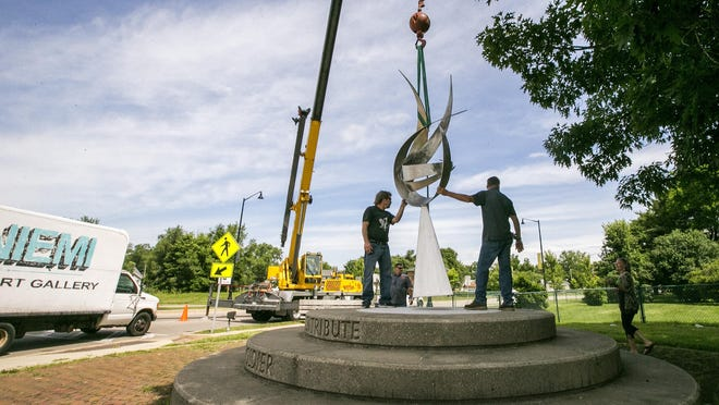 """Kenosha, Wisconsin, artist Bruce Niemi, left, helps a Ware Crane & Rigging employee install his sculpture """"The Glorious Ascent"""" on June 25, 2018, at the northeast corner of the Auburn Street roundabout in Rockford. The sculpture is one of 13 that will remain on display in Rockford until June 2021, the Rockford Area Convention & Visitors Bureau said Monday."""
