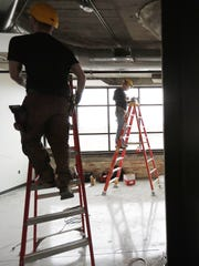Construction workers are shown at work on interior