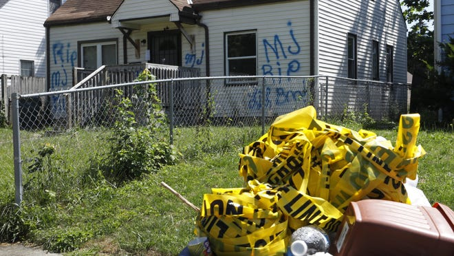 Crime scene ribbon left over from a police murder investigation fills a recycling container in front of 2282 Gerbert Road in Columbus. Fifteen-year-old Marcus Peters was killed last month at the house.