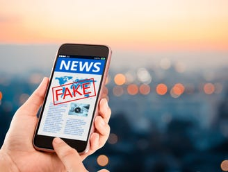 A news story on a smartphone with the word fake in red stamped over it.