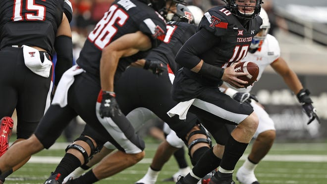 Texas Tech's Alan Bowman (10) prepares to hand off to SaRodorick Thompson on the first play from scrimmage in the season opening game Saturday against Houston Baptist. The Red Raiders lined up in a speical formation to honor the late Tommy McVay with tight end Travis Koontz (15) and slot receiver Dalton Rigdon (86) in the backfield with Thompson.