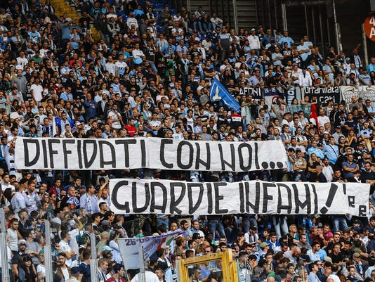 "Lazio fans display a banner reading in Italian ""Banned fans with us, vile cops"" during the Serie A soccer match between Sassuolo and Lazio at the Olympic stadium in Rome, Sunday, Oct. 1, 2017.  Lazio's problem in dealing with racism among its fans resurfaced during the Roman club's 6-1 win over visiting Sassuolo in Serie A on Sunday. After derogatory chants were directed at Sassuolo players Claud Adjapong and Alfred Duncan, the stadium announcer warned that the match could be suspended if the chants continued. (Angelo Carconi/ANSA via AP)"