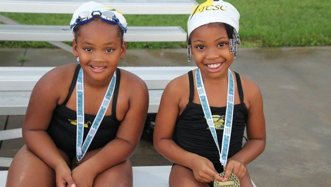 Swimmers Ross and Yvette display the medals they won.