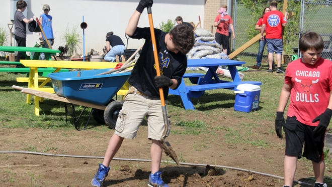 Students from Mountain Home Junior High work on the renovation project for the schools' Ability Garden.