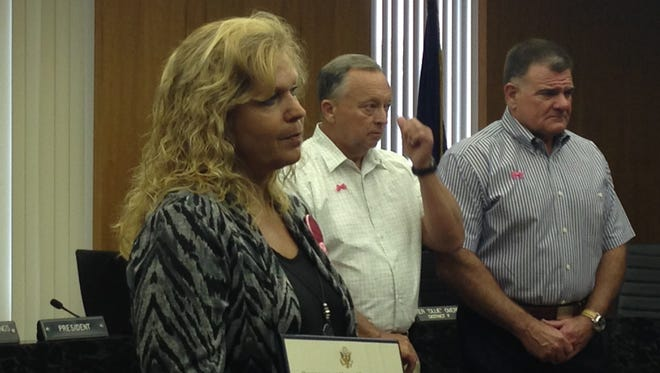 Stephanie Belgard (left), the mother of Courtney Coco, holds the commendation received Monday by the Central Louisiana Victims Rights Advocacy Group. Standing behind Belgard is Maj. Mark Baden of the Rapides Parish Sheriff's Office, who is a member of the group's committee, and Rapides Parish District Attorney Phillip Terrell.