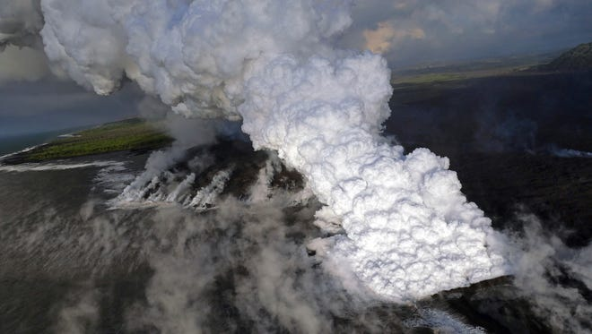 This June 6, 2018 photo from the U.S. Geological Survey shows a laze (lava haze) plume rising from the northern side of the fissure 8 lava flow margins in the former Kapoho Bay at the town of Kapoho on the island of Hawaii.