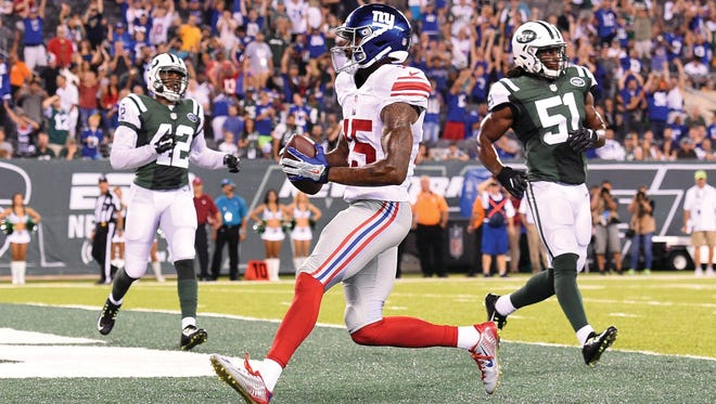 Tavarres King (No. 15) of the New York Giants runs into the end zone for  touchdown in front of Julian Stanford (No. 51) of the New York Jets during the fourth quarter at MetLife Stadium on August 27, 2016 in East Rutherford, N.J.  The Giants defeated the Jets 21-20.