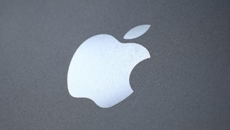 An Apple logo is seen on the back on a smartphone in London.