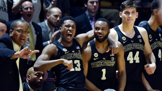 Wake Forest Demon Deacons guard Bryant Crawford (13), guard Keyshawn Woods (1), and forward Konstantinos Mitoglou (44) enjoy a win against Virginia Tech.