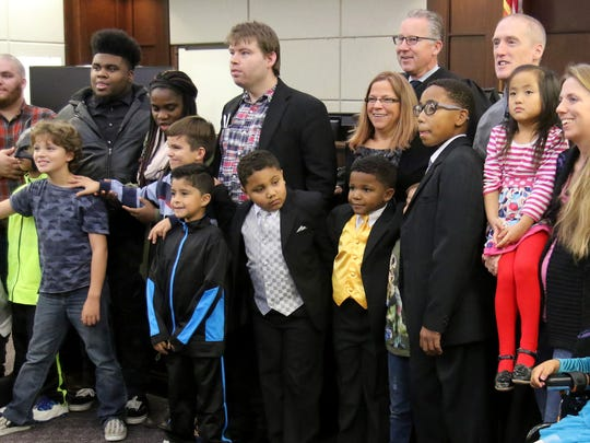 Judge Lloyd Carter poses for a photograph with the O'Brien family. With the adotion of brothers Mikey, Malachi and Isaiah, Dan and Lori O'Brien's household now includes 19 natural, foster and adopted children.