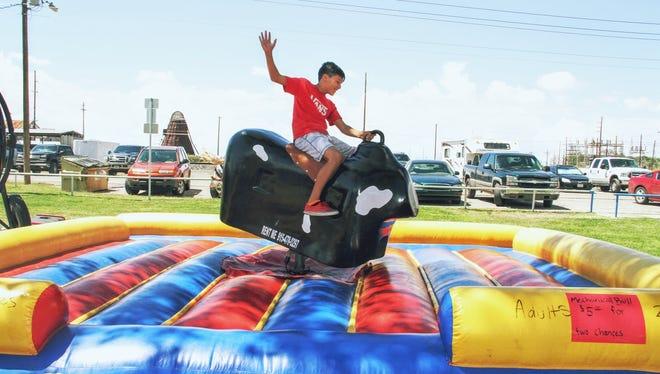 Ashton Mason  gets a bull ride at this year's Cottonwood Festival at Alameda Park.