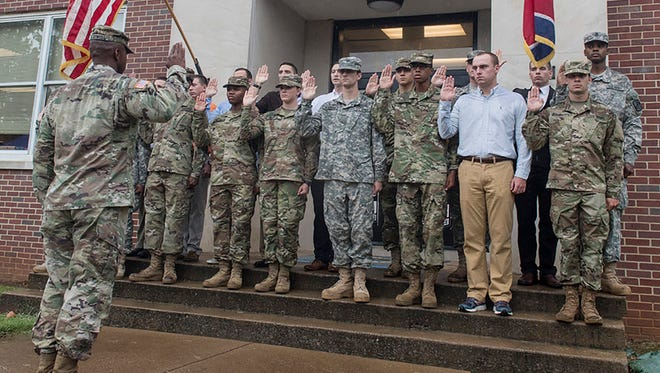 U.S. Army Lt. Col. Jackie McDowell, front, swears in 18 new ROTC cadets during the fall 2016 military science swearing-in ceremony August 19 on campus.