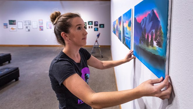 """Janelle Howard hangs artwork by Sequoia High School students for their show """"Been Relevant, Staying Relevant"""" on Tuesday, October 30, 2018. The show runs Oct. 31 to Nov. 16 and is the school's second show at Arts Visalia."""