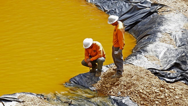 Employees with Environmental Restoration LLC work at a temporary water treatment holding facility at the Gold King Mine north of Silverton, Colo., on Aug. 10 after Environmental Protection Agency workers released more than 3 million gallons of water polluted with mine waste into the Animas River.