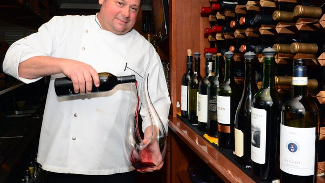 Brian Gualtieri, owner and chef of Piccola Italia Restaurant, pours wine behind the bar at the Ocean Township eatery.