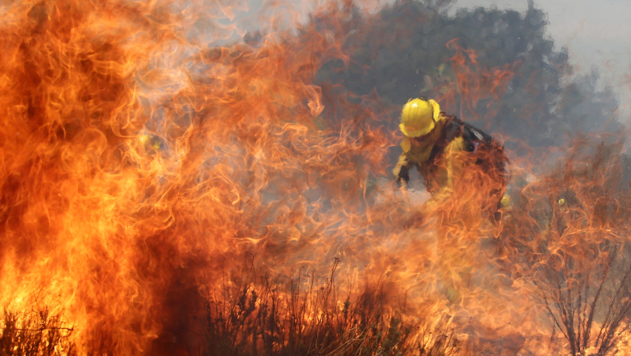 A firefighter battles a wildfire on Aug. 8 in Cabazon, Calif.