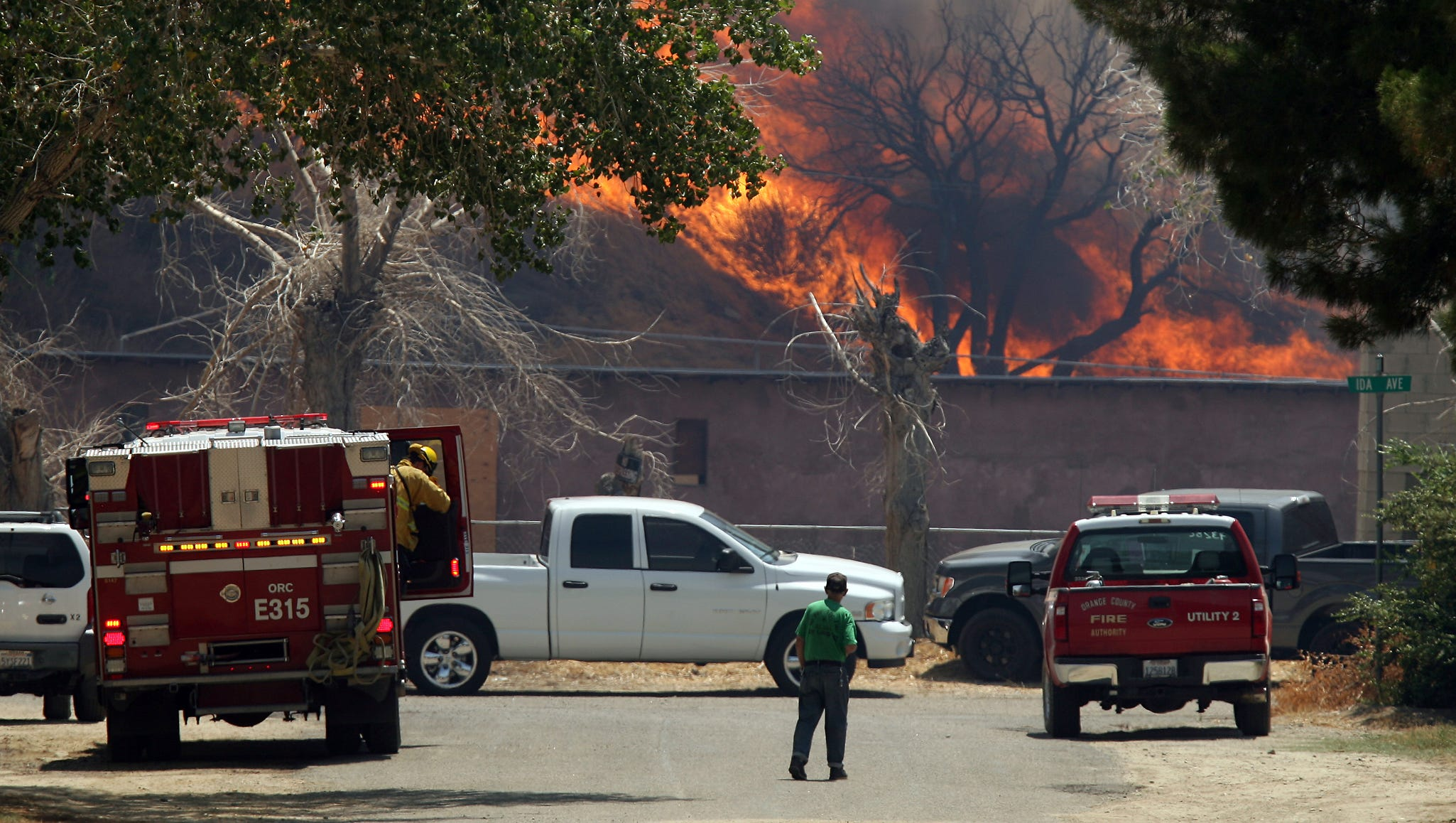 A resident, center, watches as the Silver Fire burns down a hill on Peach Street and Ida Avenue.
