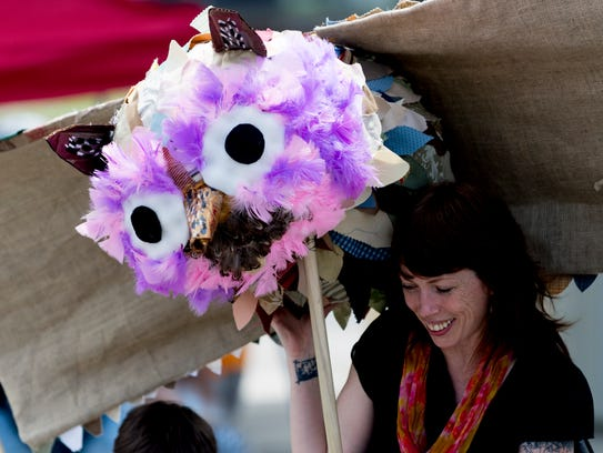 A parade member carries an owl puppet during the Appalachian