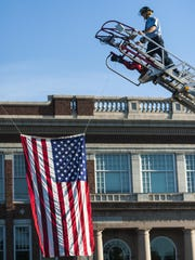 Great Falls firefighter Nate Schmidt climbs the ladder to untie the flag after the 9/11 remembrance ceremony and pancake breakfast at the Fire Station One on Friday.