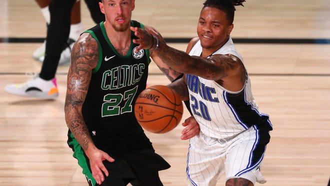Celtics center Daniel Theis, left, battles Magic guard Markelle Fultz during overtime in Sunday's game in Florida.
