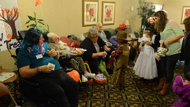 Kids pass through a line of residents and employees collecting candy while trick or treating at Valley View Healthcare Center in Fremont on Thursday, Oct 23, 2014