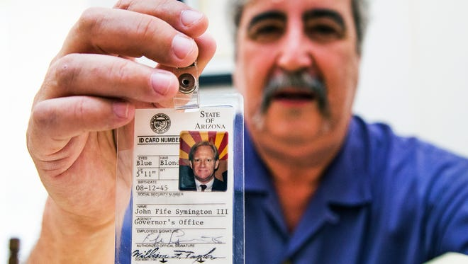 Arizona Capitol Museum Historian Jack August holds up Gov. Fife Symington's I.D. badge from his time in office.