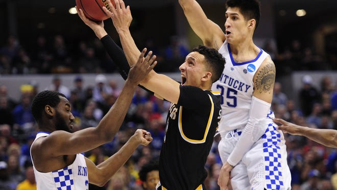Wichita State guard Landry Shamet (11) attempts a shot between Kentucky defenders Derek Willis, right, and Dominique Hawkins during Sunday?s second-round game of the NCAA Tournament in Indianapolis. Kentucky defeated Wichita State 65-62.