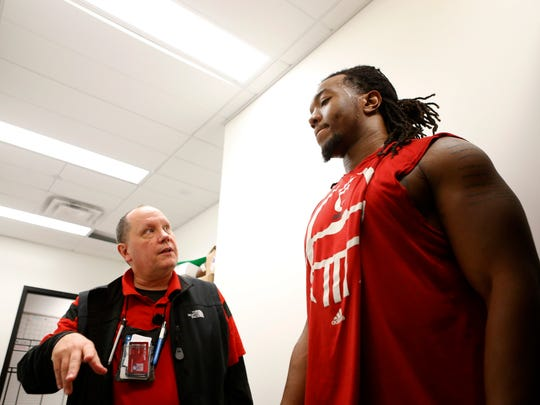 Dr. Joseph Clark talks to Silverberry Mouhon, University of Cincinnati senior and defensive lineman,  during an exercise to train his peripheral vision at UC Wednesday, December 16, 2015.  Clark helped design trainings to prevent concussions in their athletes. Athletes are able to widen their peripheral vision by a few degrees, which helps them anticipate being hit.