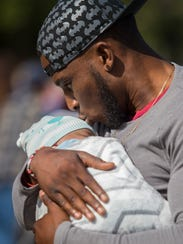 Fort Myers resident Ken Diesel kisses his 4-month old