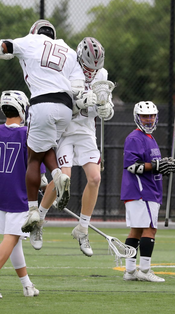 Garden City's James Basile and Trevor Yeboah-Kodie celebrate Garden City's first goal in front of John Jay's Thomas Feinstein and Isiah Rust during a New York State Class B lacrosse state semifinal game Adelphi University in Garden City, Long Island June 6, 2018. Garden City defeated John Jay 14-4.