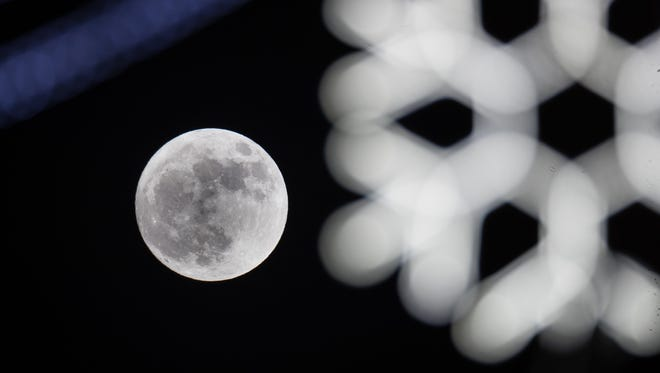 "The supermoon rises behind seasonal lights on display in Wells, England. The supermoon which is known by Native American tribes as the ""Wolf Moon"", is when the moon is closest to Earth, known as the perigee."