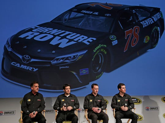 Joe Garone, left, president and general manager of Furniture Row Racing, sits with driver Martin Truex Jr, second from left, crew chief Cole Pearn, second from right, and professional bull rider Luke Snyder, right, during the Charlotte Motor Speedway NASCAR Media Tour in Charlotte, N.C., Tuesday, Jan. 19, 2016. (AP Photo/Chuck Burton)