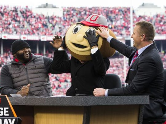 Former Ohio State Buckeyes players Orlando Pace (l) and Kirk Herbstreit (r) laugh as ESPN College Gameday host Lee Corso dons the head of Brutus Buckeye, signifying his pick for the game against the Michigan Wolverines at Ohio Stadium. Ohio State won the game 30-27 in double overtime. Mandatory Credit: Greg Bartram-USA TODAY Sports